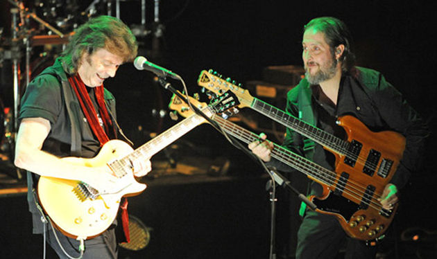 Lee (right) wields a double-neck onstage with Steve Hackett