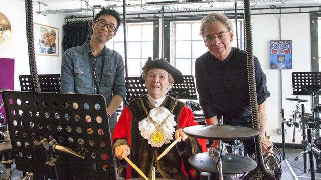 ACM drum tutor Joe Yoshida and Bill Bruford give Mayor of Guildford Jennifer Jordan a drumming master class.