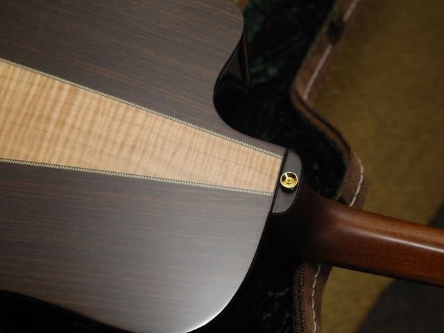 The back insert is a striking flash of flamed maple.