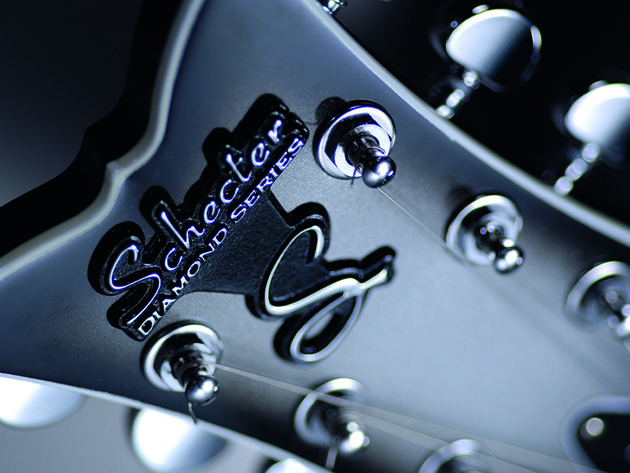 Fishtail headstock with raised metal logo.