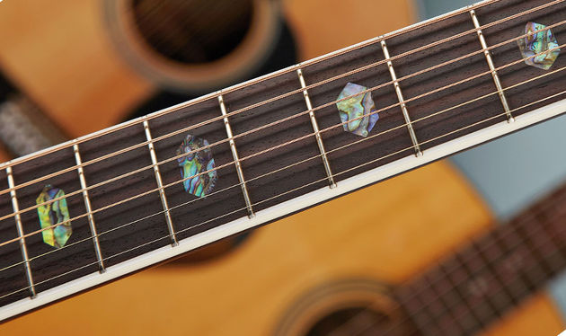 Its upmarket style means tasteful bling, including this white bound fingerboard with its abalone hexagon inlays