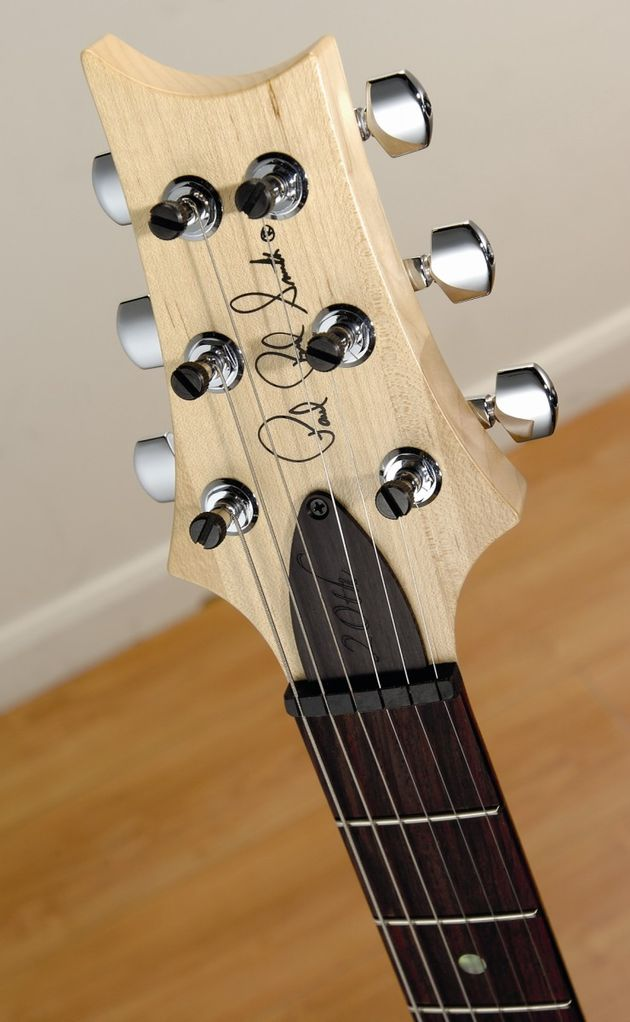 The maple headstock creates a contrast with the guitar's rosewood fingerboard