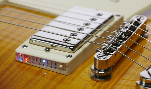 Press a button on the bridge pickup mounting ring to activate the guitar's built-in chromatic tuner