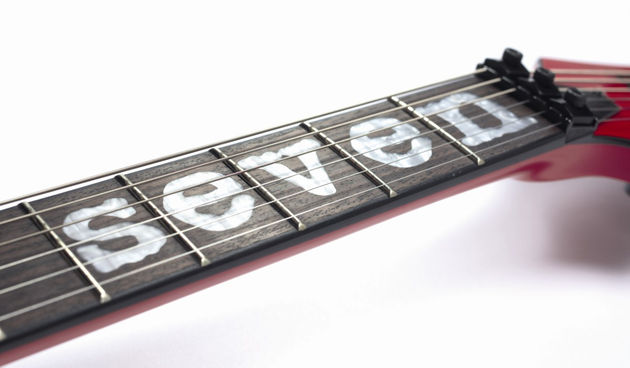 The rosewood fingerboard is inlaid with the legend 'Seven'.