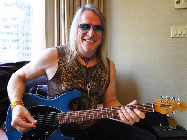 Happy? You bet Steve Morse is happy. He's holding a guitar, isn't he?