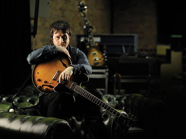 The Elbow guitarist cradles his beloved Gibson ES-335