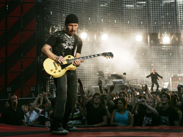 The Edge plays his white Les Paul Custom